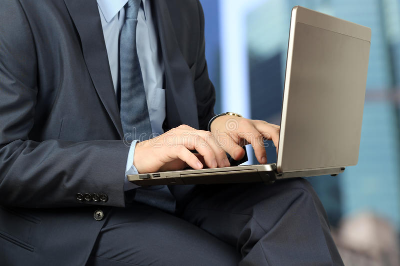 Young businessman working with a laptop, sitting outside, mod. Ern building behind stock photo