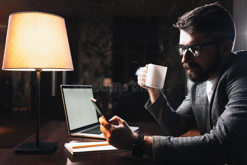 Young businessman working at modern office at night royalty free stock image