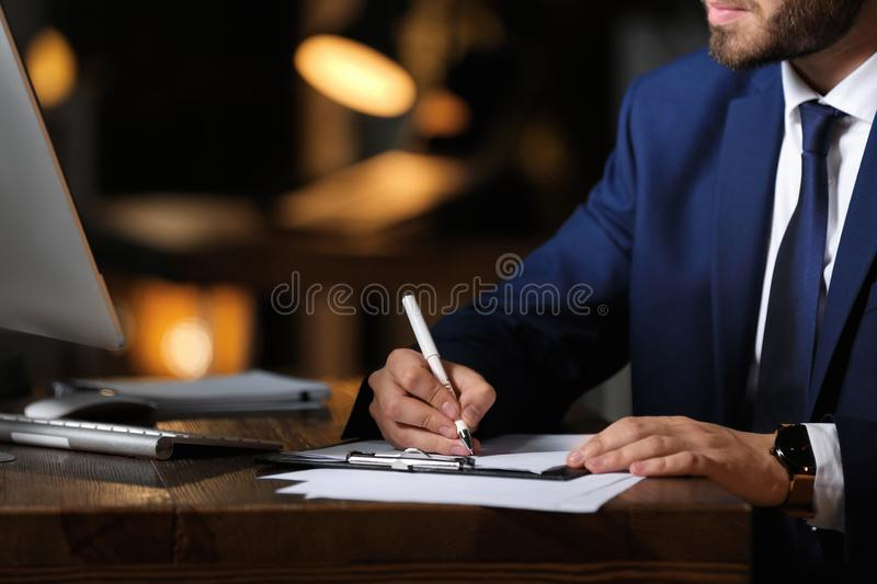 Young businessman working in office alone at night. Closeup royalty free stock images