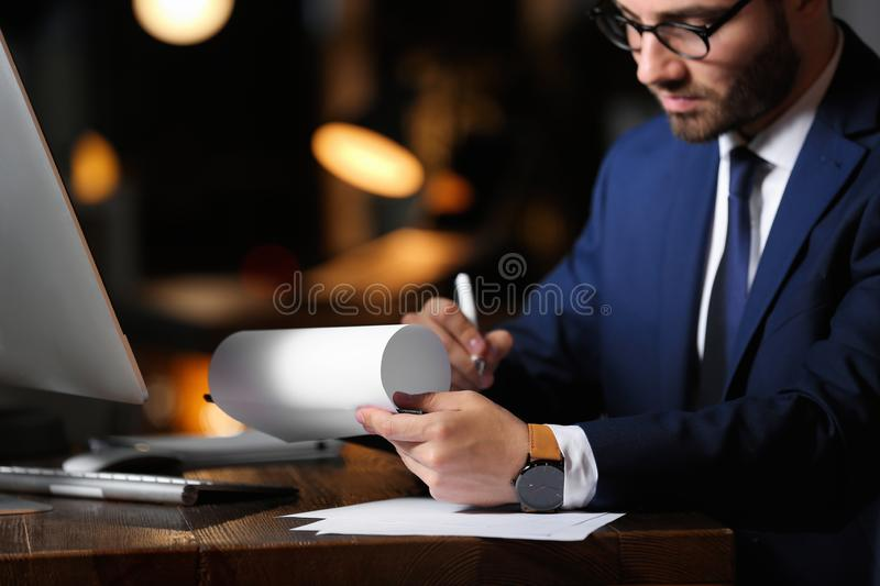 Young businessman working in office alone at night. Closeup stock image