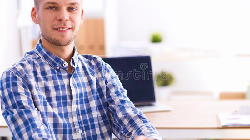 Young businessman working in office, sitting at desk. Isolated stock photography