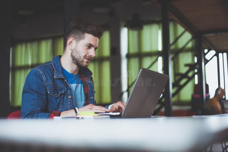 Young businessman working in office, sitting at desk, looking at laptop computer screen, smiling.  stock photos
