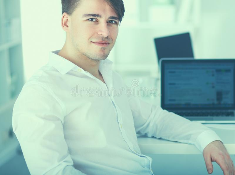Young businessman working in office, sitting at desk royalty free stock photos