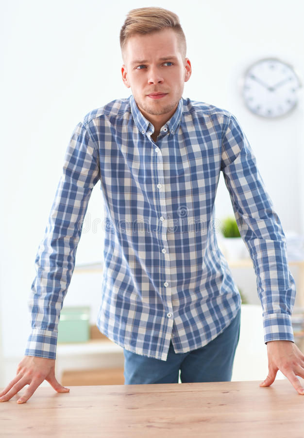 Young businessman working in office, standing near stock images