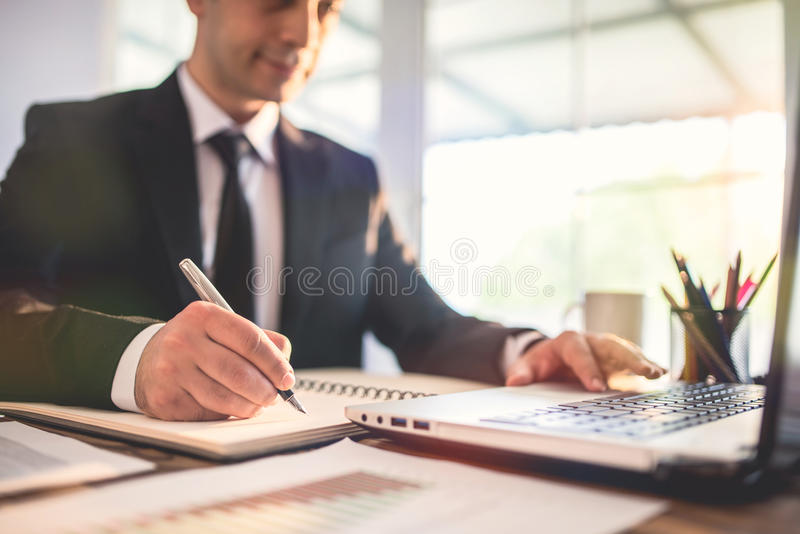 Young Businessman Working In Office And Taking Notes stock photos
