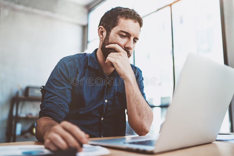 Young businessman working at sunny work place on laptop while sitting at the wooden table.Blurred background.Horizontal. Young businessman working at sunny work stock photos