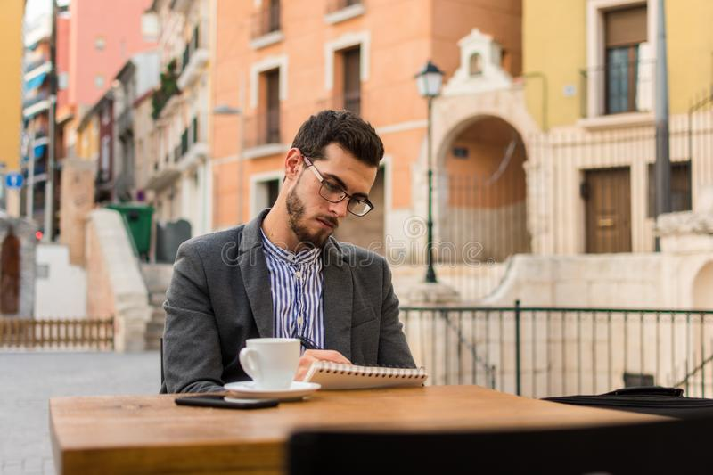 Young businessman is writing in his notebook in a bar terrace stock photos