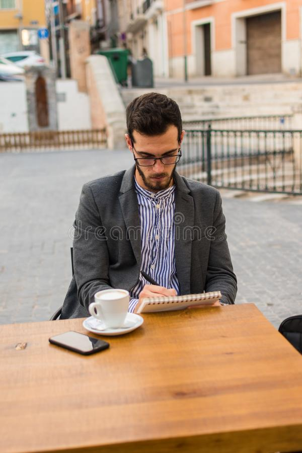 Young businessman is writing in his notebook in a bar terrace royalty free stock images