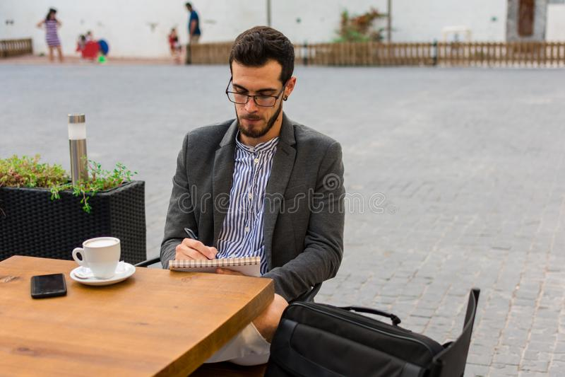 Young businessman is writing in his notebook in a bar terrace royalty free stock photos