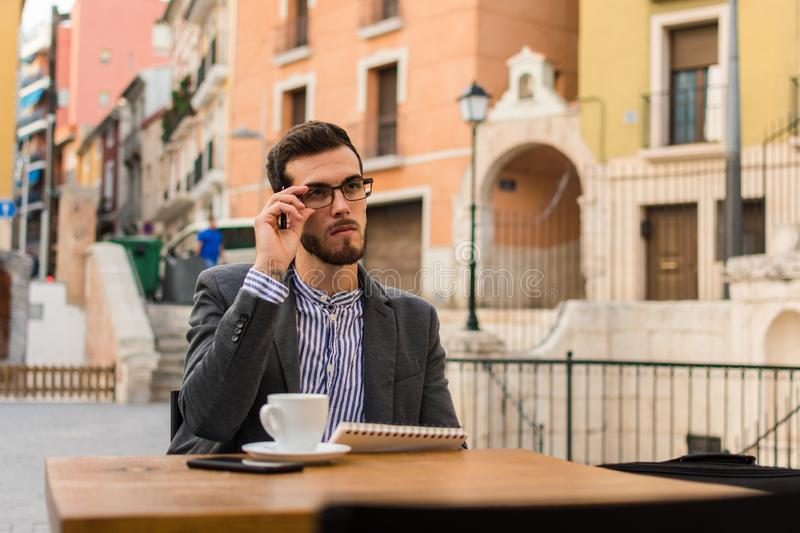 Young businessman is writing in his notebook in a bar terrace stock photography