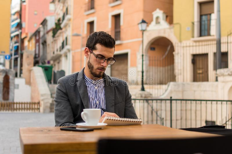 Young businessman is writing in his notebook in a bar terrace royalty free stock photo