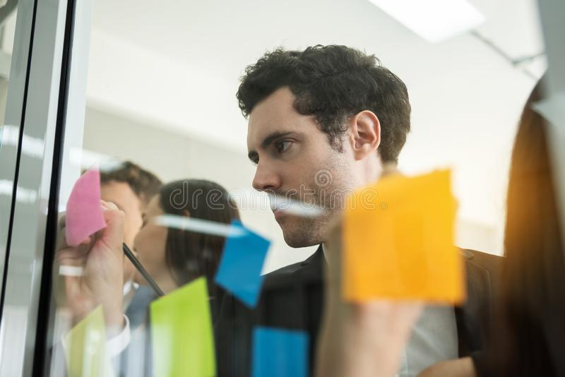 Young Businessman is writing new ideas at sticky notes. stock image