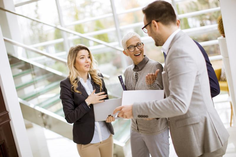 Young businessmen with senior and young businesswomen in office stock images