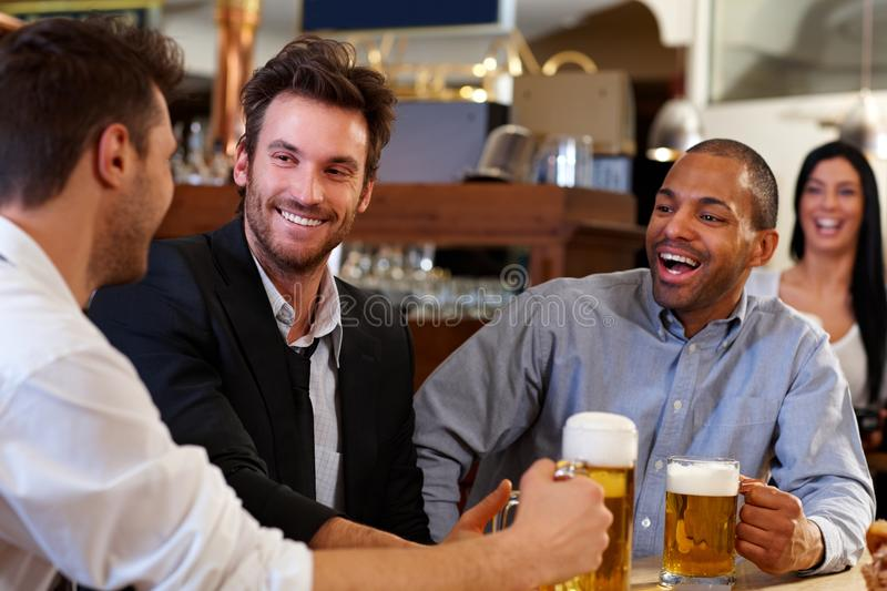 Young businessmen drinking beer at pub. Happy young businessmen drinking beer and talking at pub after work. Looking at each other smiling royalty free stock photo