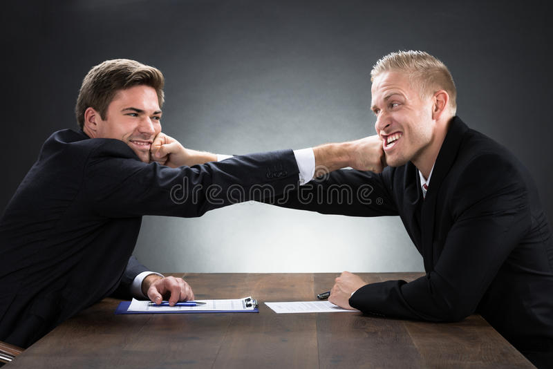 Young Businessmen Fighting At Wooden Desk. Against gray background stock image