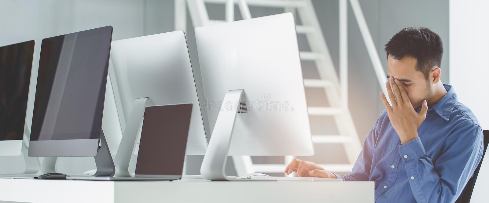 Young businessmen in rest his eyes stress. Sit in front of modern office computer. royalty free stock photos
