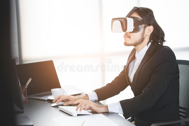 Businessmen viewing the contents of VR device. Young businessmen standing and viewing the contents of the virtual reality device, which is a technology of the royalty free stock photos