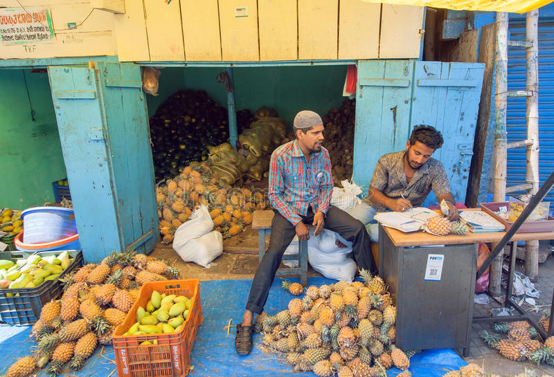 Young businessmen traders of pineapples and oranges on market of indian city royalty free stock photography