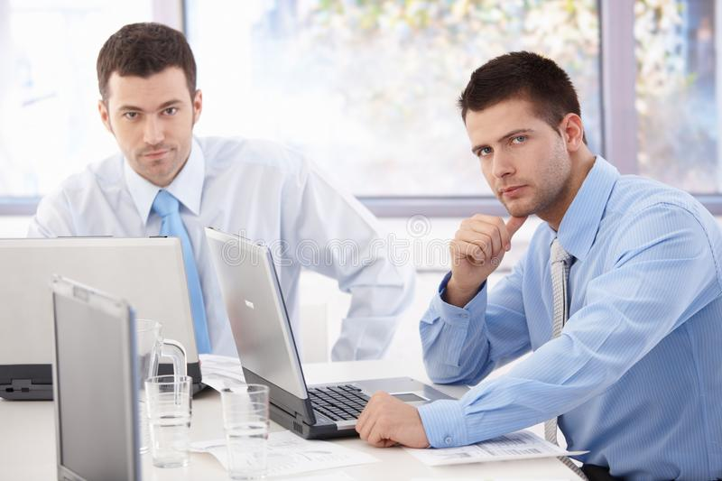 Young businessmen working at meeting table. Young businessmen sitting at meeting table, working on laptop stock images