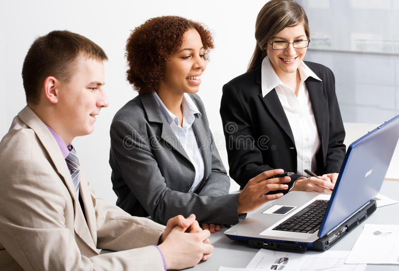 Young businesspeople. Three young businesspeople looking at monitor stock photo