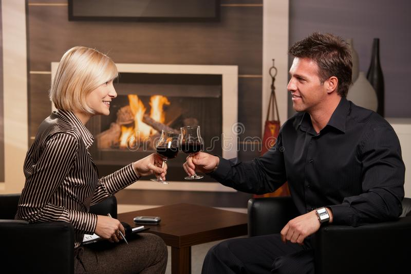Young businesspeople clinking wine glasses. Happy young businesspeople clinking wine glasses in business club royalty free stock photography