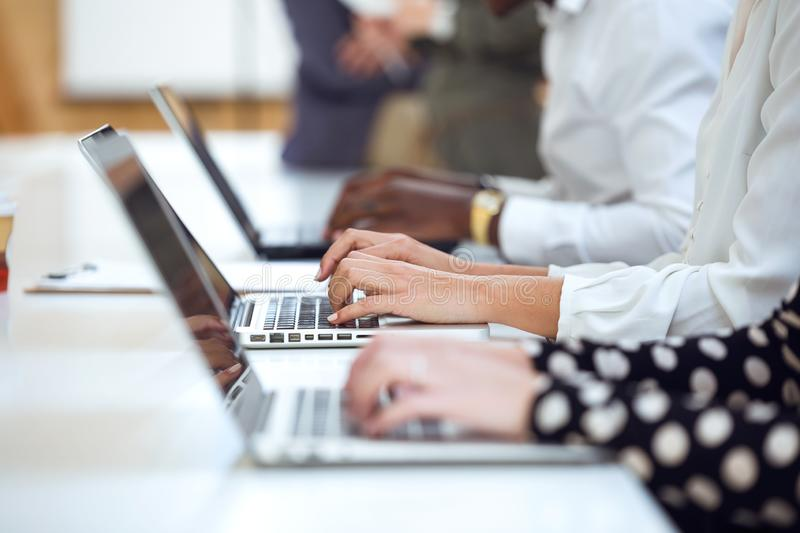 Young businesspeople hands working on their laptop on coworking place. Close up of young businesspeople hands working on their laptop on coworking place royalty free stock photos