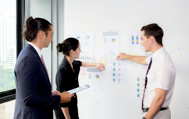 Young businesspeople pointing towards graph with present profit while giving presentation in office. The young businesspeople pointing towards graph with royalty free stock images