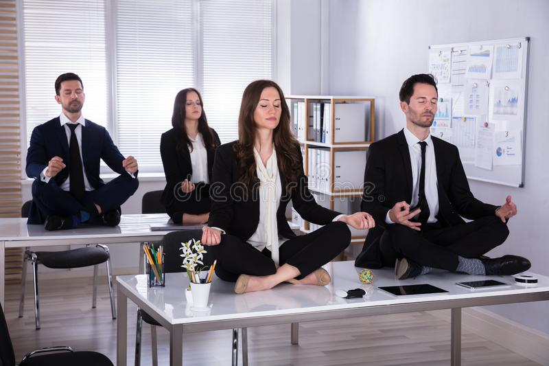 Businesspeople Meditating In Office royalty free stock photography