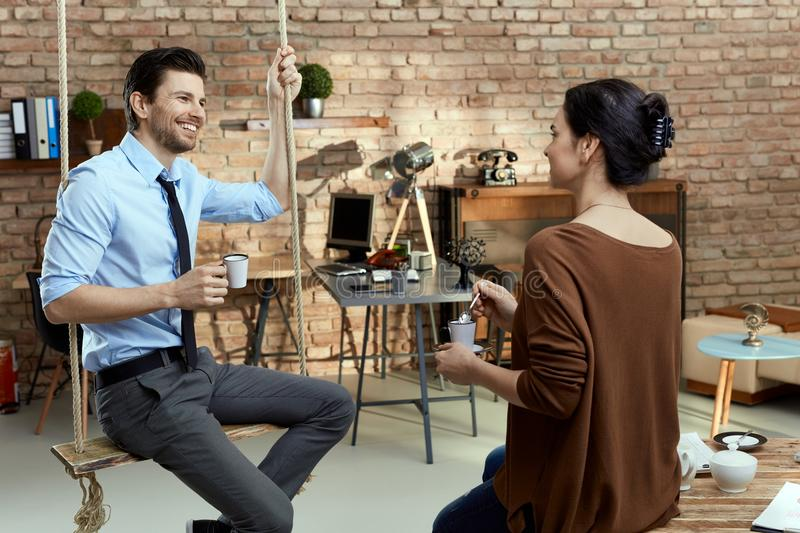 Colleagues talking in office stock images