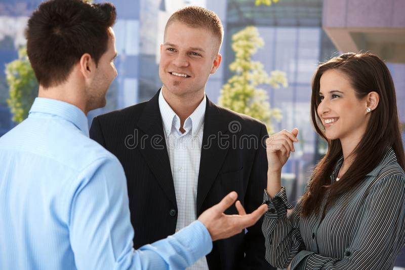 Young businesspeople talking outside of office stock photo