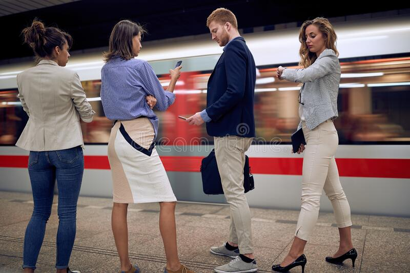 Young businesspeople watching at their cell phones, wrist watch. Missed train in a subway. time running fast concept stock images