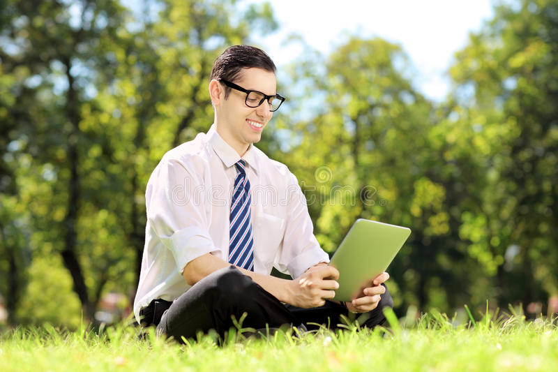 Young businessperson with glasses seated on a grass working on a royalty free stock photo