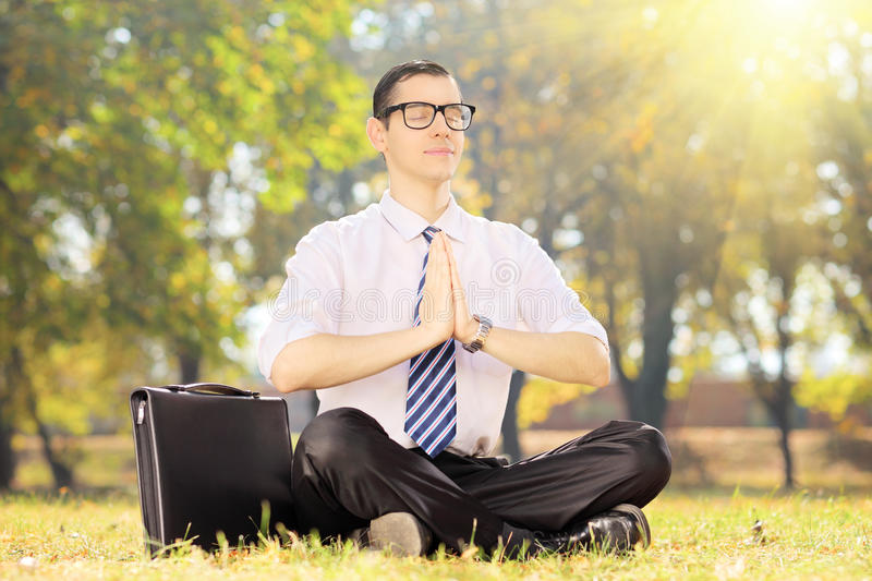 Young businessperson with tie doing yoga seated on grass in a pa. Young businessperson with tie doing yoga exercise seated on a green grass in a park royalty free stock photography