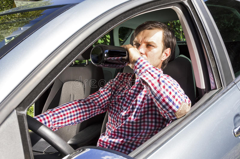 Young businesssman drinking alcohol while driving royalty free stock photography