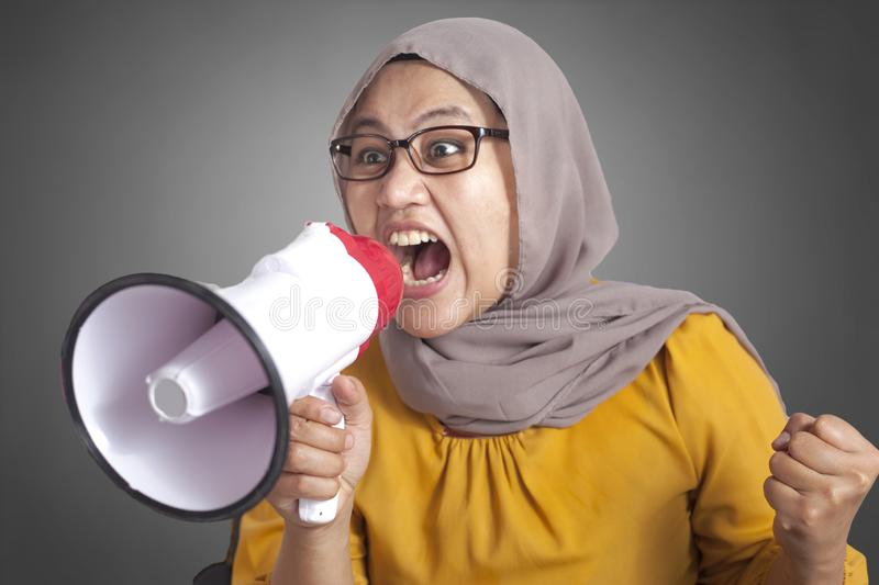 Young Businesswoman Angry, Screaming Using Megaphone. Young Asian muslim businesswoman wearing hijab screaming with megaphone, angry expression. Close up body stock photography