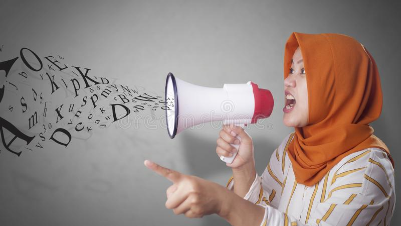 Young Businesswoman Angry, Screaming Using Megaphone. Young Asian businesswoman wearing suit and hijab screaming on megaphone with an angry expression. Close up stock images