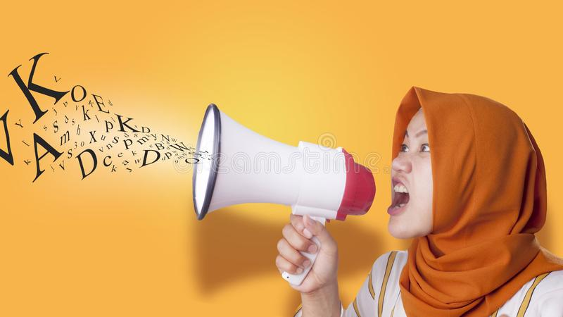Young Businesswoman Angry, Screaming Using Megaphone. Young Asian businesswoman wearing suit and hijab screaming on megaphone with an angry expression. Close up royalty free stock images