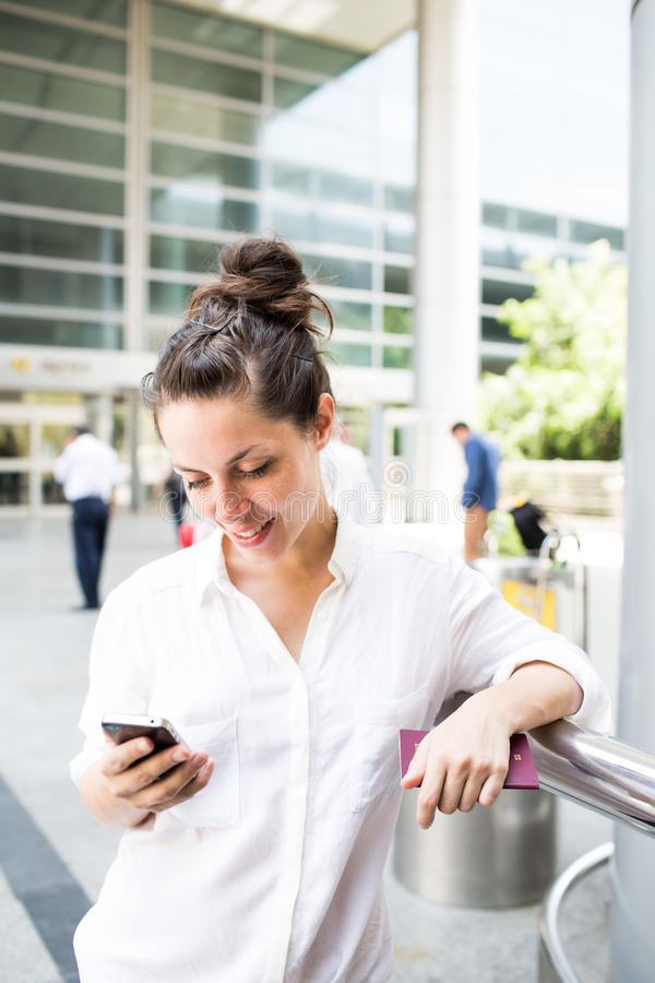 Young businesswoman. Beautiful and happy young businesswoman looking on cell phone in front of the airport stock photography