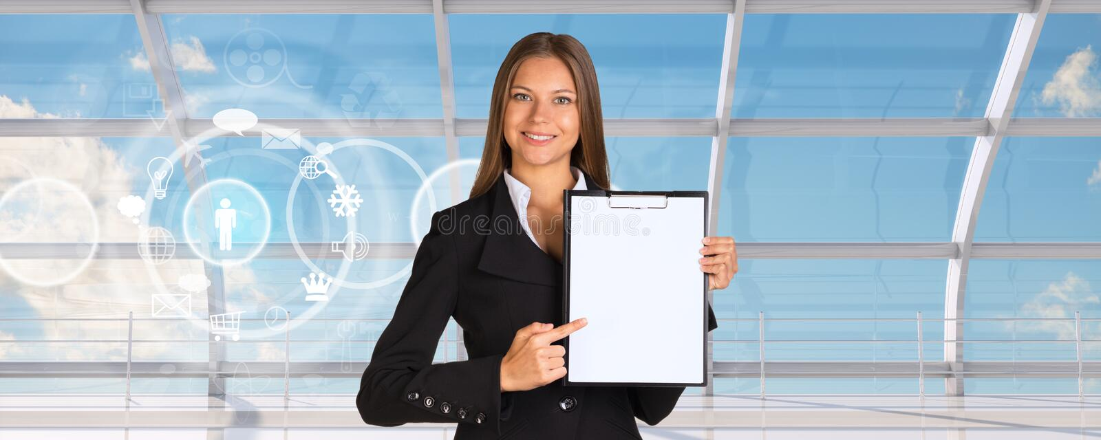 Young businesswoman in black suit. With folder and blank paper with icons on window blue sky background royalty free stock images
