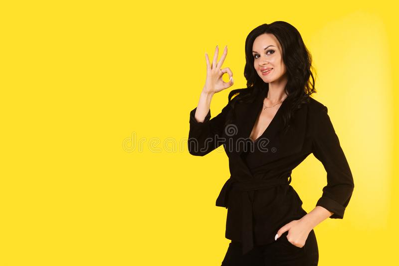 Young businesswoman in black suit shows sign ok isolated on a yellow background royalty free stock photography