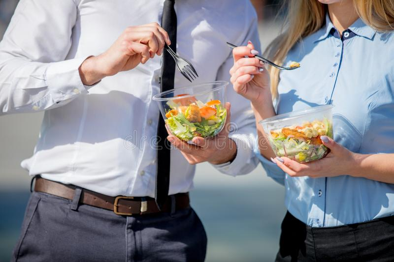 Young businesswoman and businessman eating together salad. In lunch box on outdoor royalty free stock image