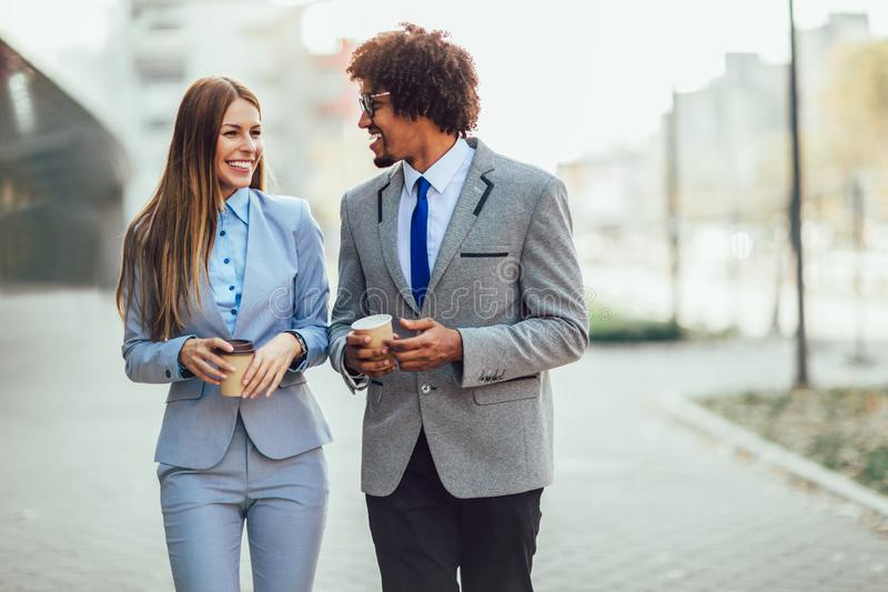 Young businesswoman and businessman having a coffee break. They are looking at each other, talking and drinking coffee stock photo