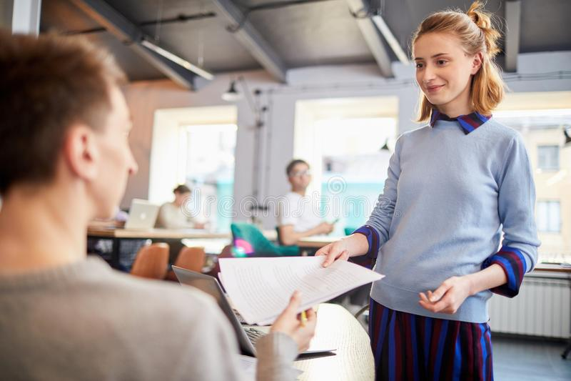 Thank you. Young businesswoman in casualwear giving papers back to colleague after reading them royalty free stock photos
