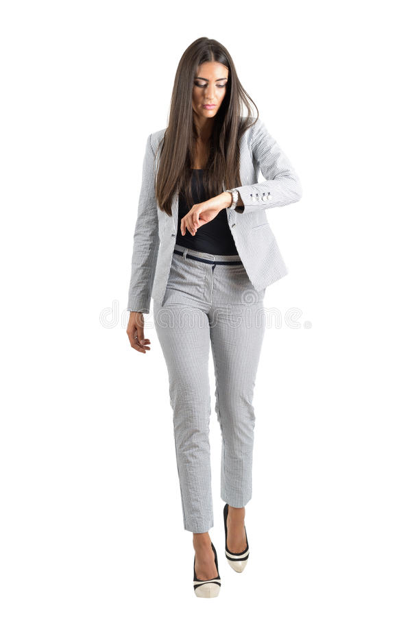 Young businesswoman checking hand watch walking forward in the rush. royalty free stock photo