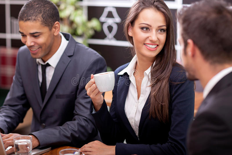 Young businesswoman with cup of coffee communicating with his co royalty free stock images