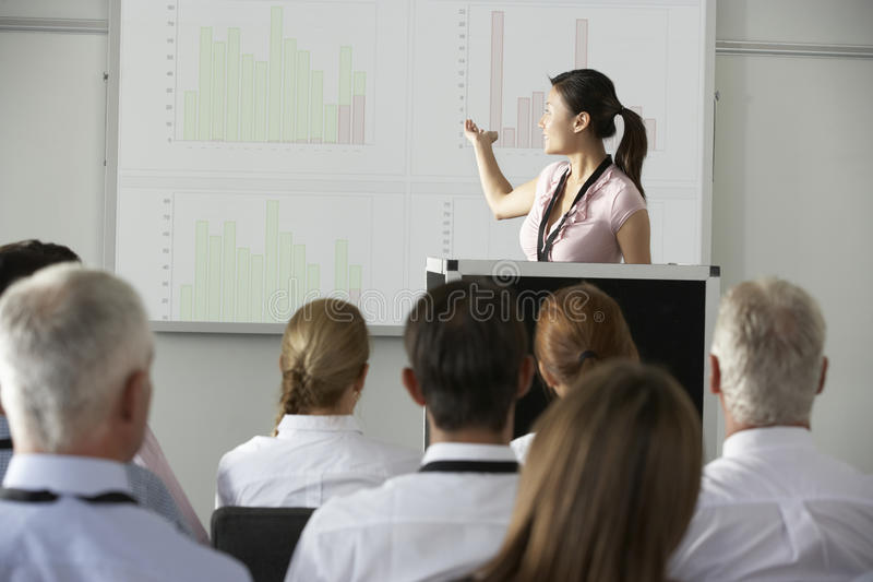 Young Businesswoman Delivering Presentation At Conference stock image