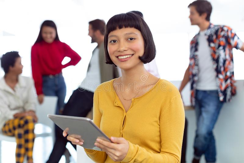 Young businesswoman with digital tablet standing in a modern office. Front view of happy young Asian businesswoman with digital tablet standing in a modern stock photography