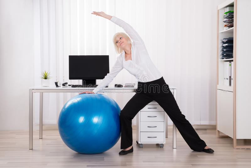 Businesswoman Doing Stretching Exercise. Young Businesswoman Doing Stretching Exercise In Office royalty free stock photos