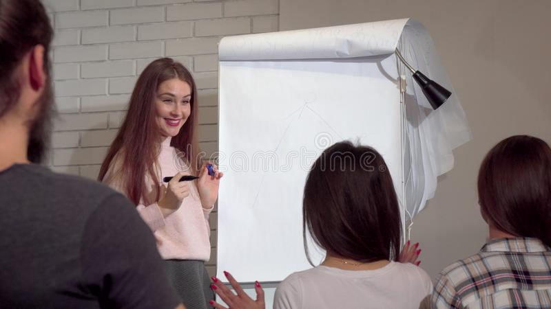Young businesswoman drawing on flipchart, leading business conference. Attractive female entrepreneur having business presentation with her coworkers stock images