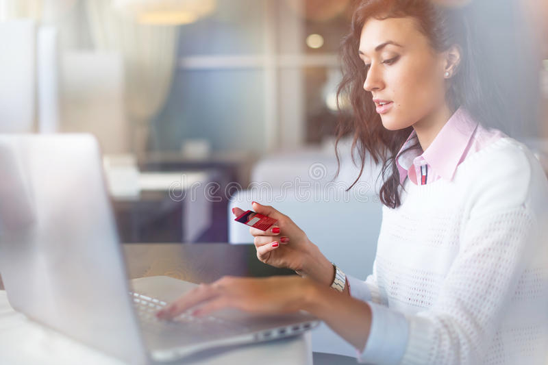 Young businesswoman drinking coffee and using laptop computer in cafe doing online shopping, holding credit card. royalty free stock photo